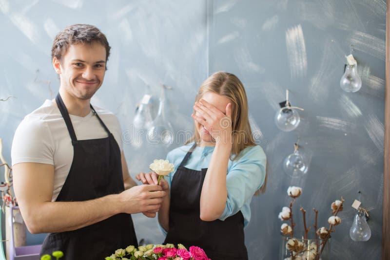 采取从她的男朋友的窘迫女孩白色玫瑰 免版税库存图片