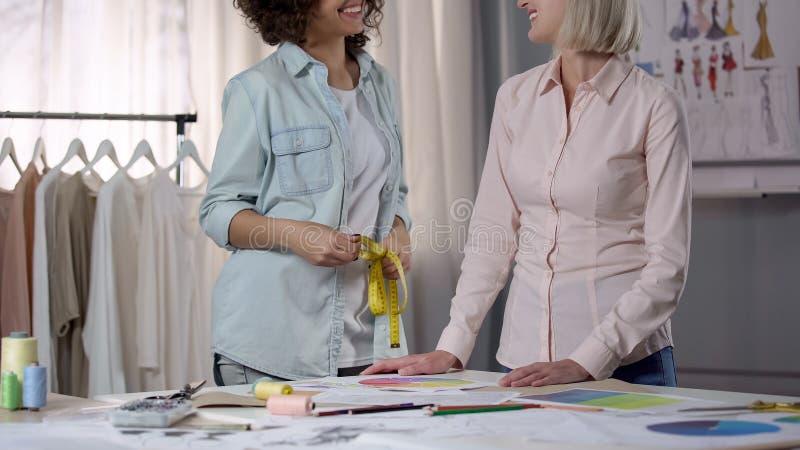 采取从客户的裁缝测量剪裁的期望衣裳 免版税库存图片