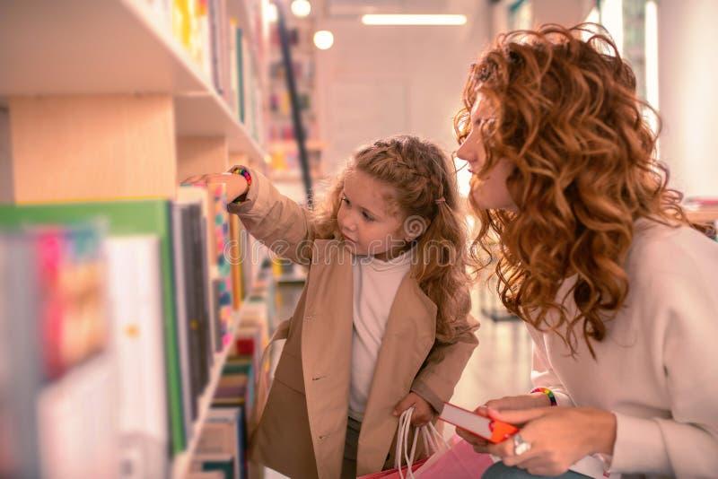 采取从架子的美丽的白肤金发的女孩书 免版税库存照片