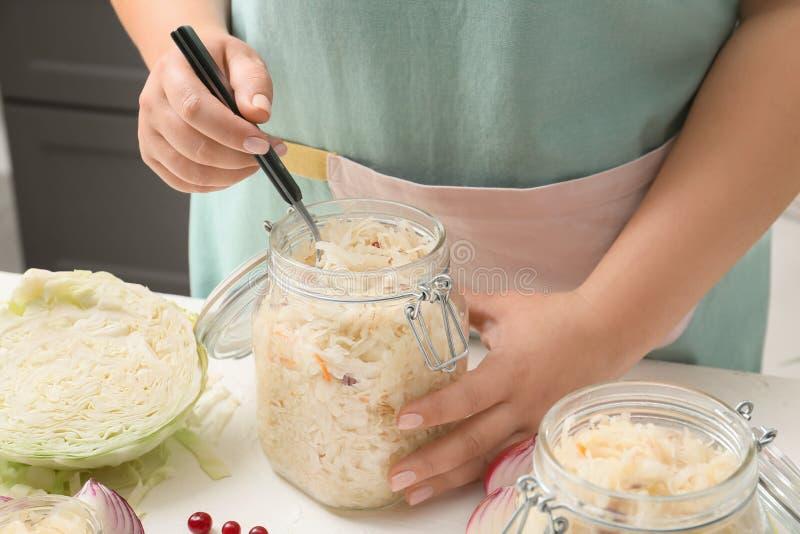 采取从瓶子的妇女自创德国泡菜有叉子的在桌上 免版税库存照片