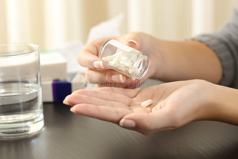 采取从瓶的妇女一个药片 库存照片
