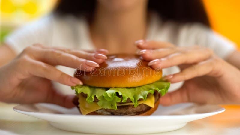 采取从白色板材特写镜头,胆固醇的女性手鲜美乳酪汉堡 库存照片
