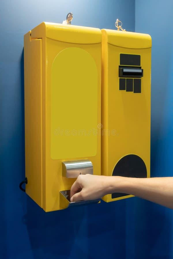 采取从票据更换者机器的妇女的手硬币在黄色颜色 免版税库存照片