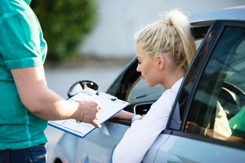 采取从辅导员的妇女驾驶课 免版税图库摄影