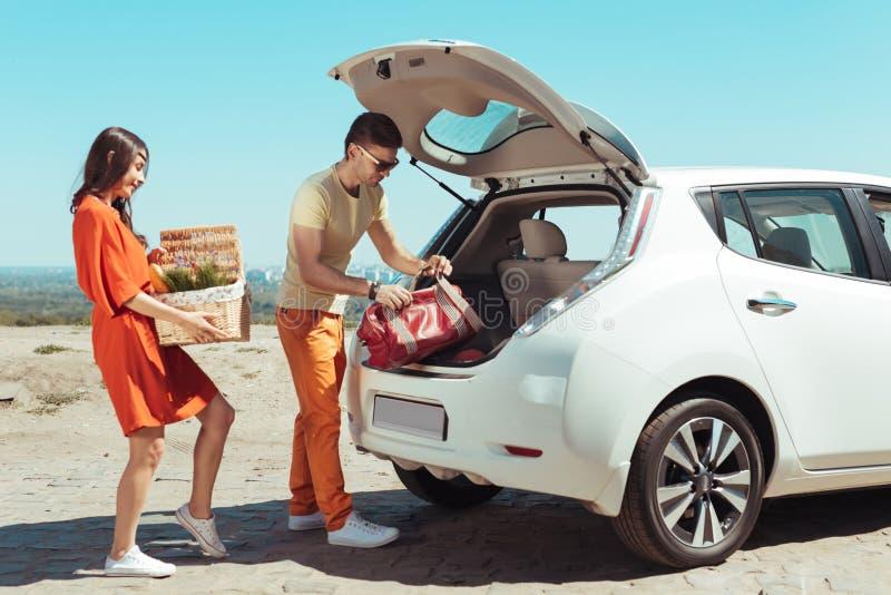 采取他们的事的现代夫妇在汽车外面,当去去野餐时 免版税库存照片