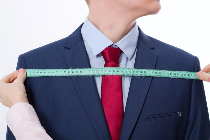 采取企业夹克衣服的裁缝的特写镜头图象测量 在红色领带的商人和在被隔绝的演播室的蓝色衣服 免版税库存图片