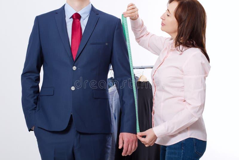 采取企业夹克衣服的裁缝的特写镜头图象测量 在红色领带的商人和在被隔绝的演播室的蓝色衣服 库存图片