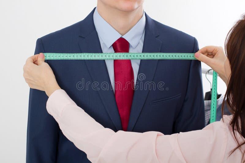 采取企业夹克衣服的裁缝的特写镜头图象测量 在红色领带的商人和在被隔绝的演播室的蓝色衣服 免版税库存照片