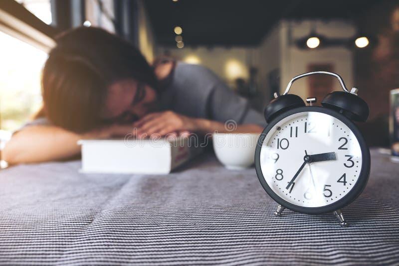 采取休息的亚裔妇女,当读与黑闹钟的一本书在桌时 库存照片