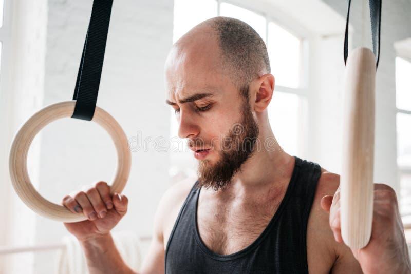 采取休息的体操运动员男性接近的画象在强烈的垂度圆环锻炼以后在健身房 图库摄影
