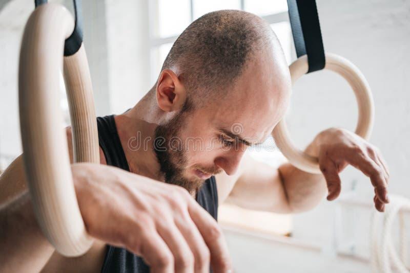 采取休息的体操运动员男性接近的画象在强烈的垂度圆环锻炼以后在健身房 免版税库存照片