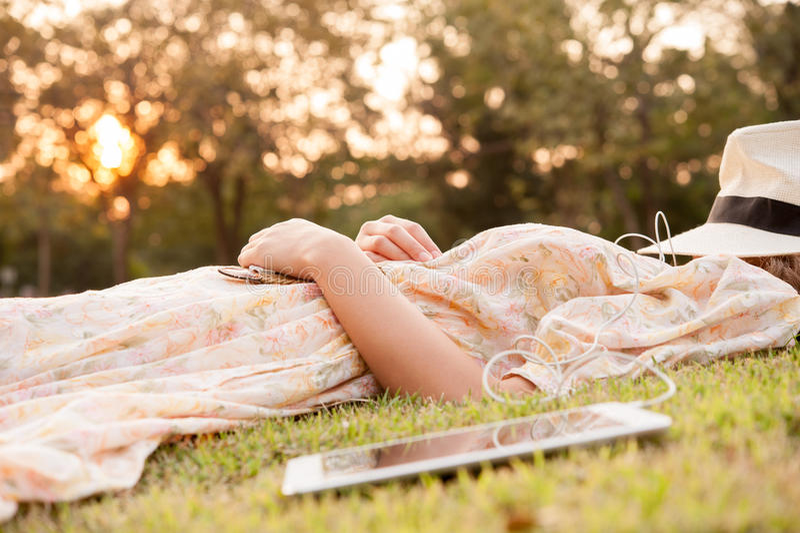 采取休息的少妇在有帽子的公园在与片剂的面孔 库存图片