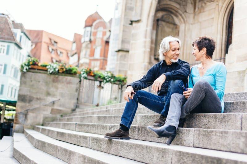 采取休息的资深夫妇在教会旁边 库存照片