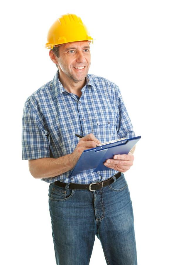 采取佩带的工作者的安全帽附注 免版税库存照片
