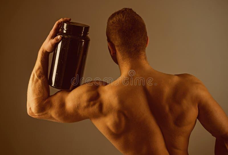 采取健康饮食的维生素 有维生素补充的肌肉人 坚强男人举行补充瓶 图库摄影