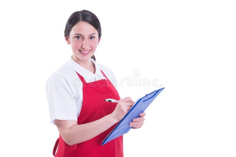 采取关于剪贴板的勤勉女性卖主笔记 免版税库存图片