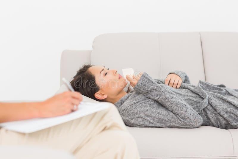 采取关于她哭泣的患者的治疗师笔记长沙发的 免版税库存照片