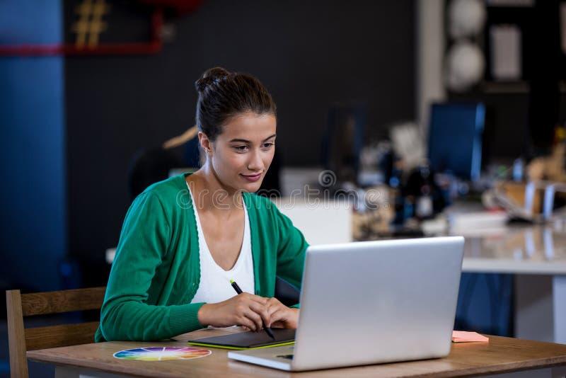 采取关于她的片剂计算机的女实业家笔记 免版税库存照片