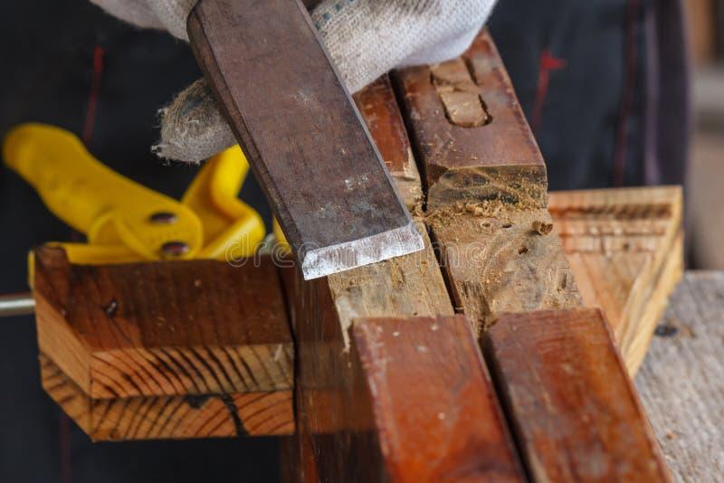 采取凿子的木匠的手削尖木板条 免版税库存照片