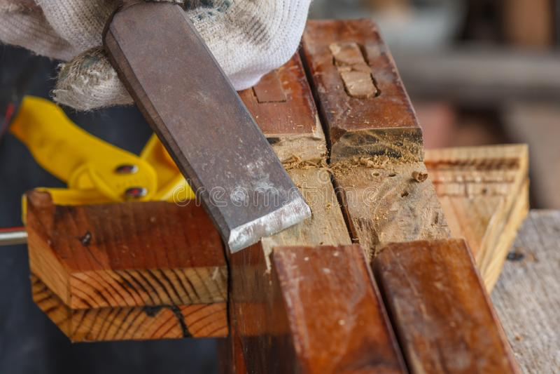 采取凿子的木匠的手削尖木板条 免版税库存图片