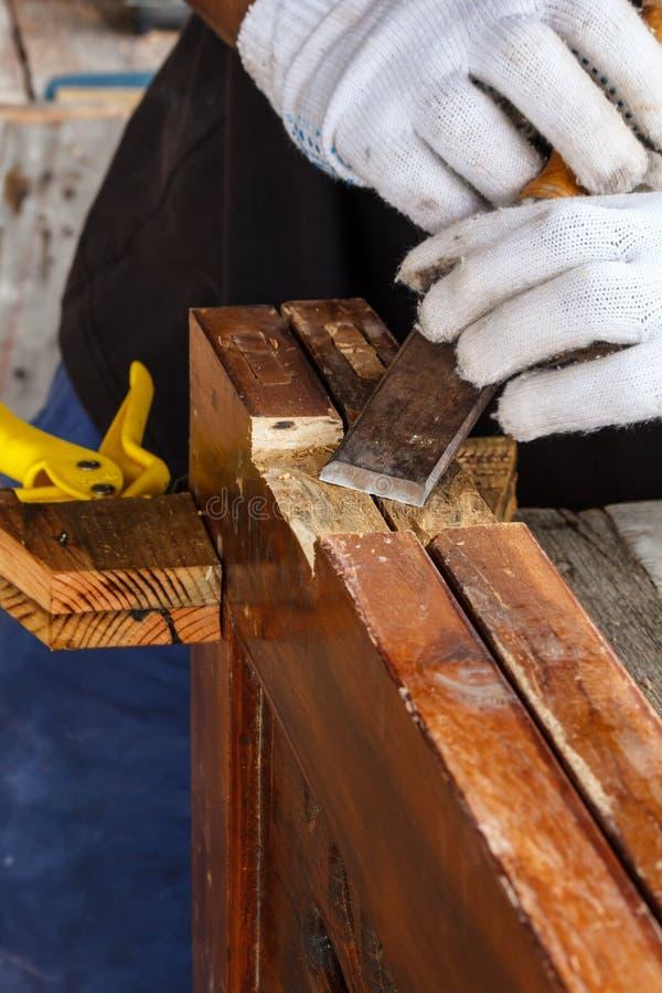 采取凿子的木匠的手削尖木板条 免版税图库摄影