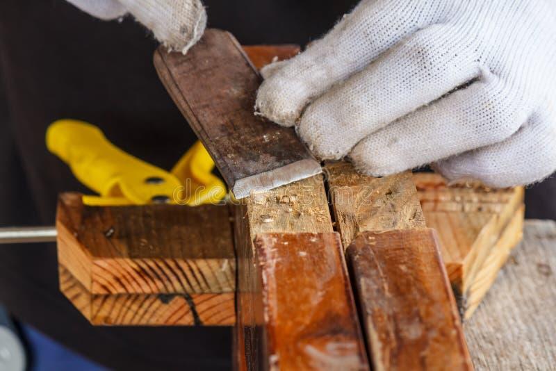 采取凿子的木匠的手削尖木板条 库存图片