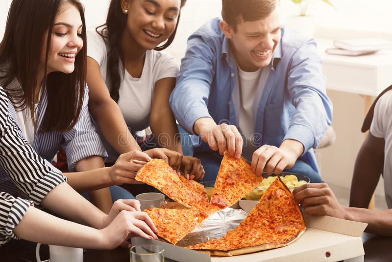 采取切片从纸板箱的热的比萨的朋友 免版税库存照片
