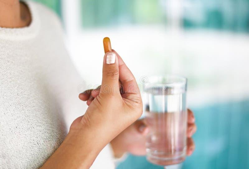 采取医学医疗保健和人概念-妇女藏品药片胶囊补充食物和采取与在手中水玻璃 免版税库存图片