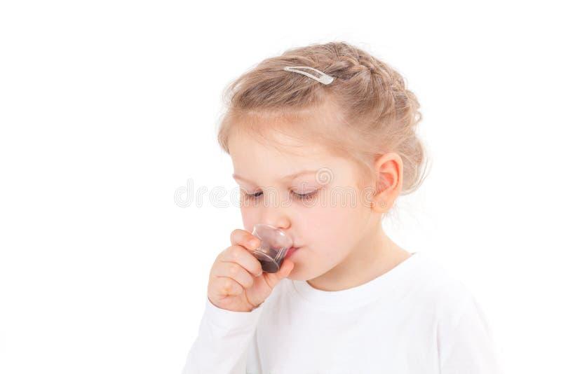 采取咳嗽糖浆的病的女孩 免版税图库摄影