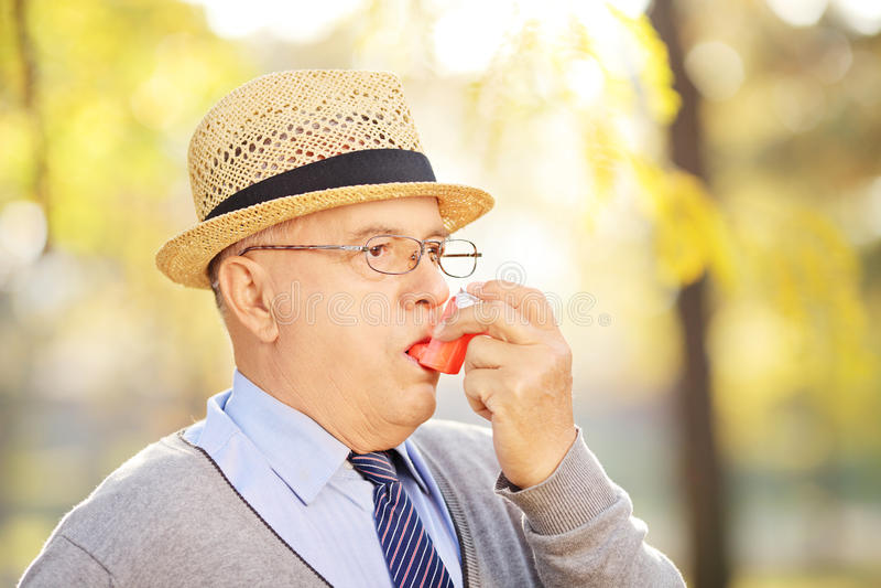 采取哮喘治疗的资深绅士在公园 库存照片