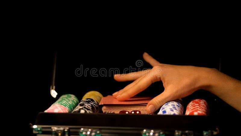 采取啤牌卡片的副主持人的女性手成交,赌博的瘾,打赌 库存照片