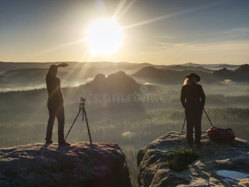 采取图片和谈话的两个徒步旅行者在山顶部 两位摄影师 皇族释放例证