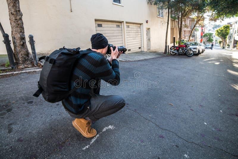 采取图片在他的期间在城市街道上的摄影师旅行 免版税库存图片