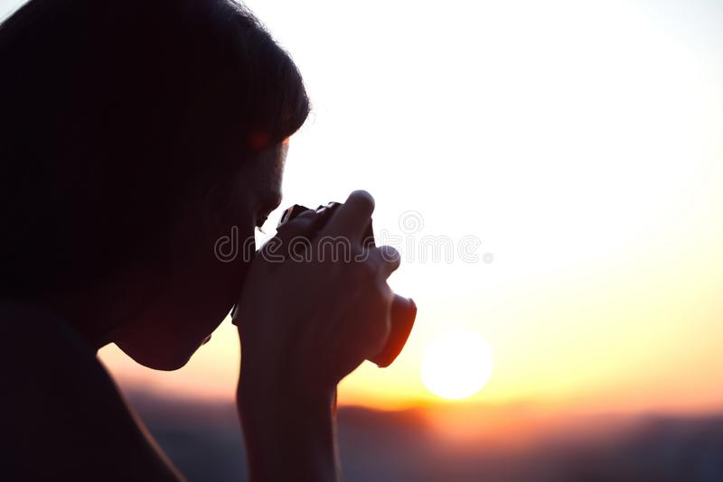 采取图片在袖珍相机的女孩摄影师剪影落日 日落背景 免版税库存图片