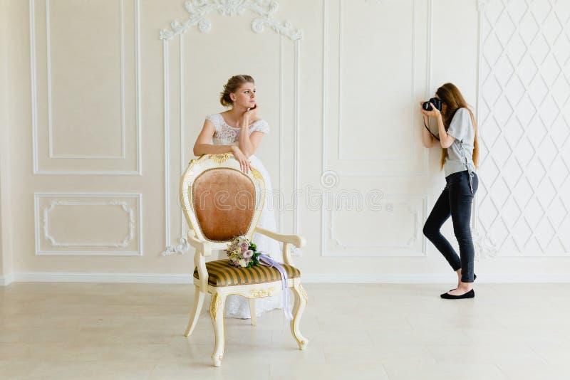 采取图片年轻性感的新娘的摄影师在演播室在椅子附近 免版税库存图片