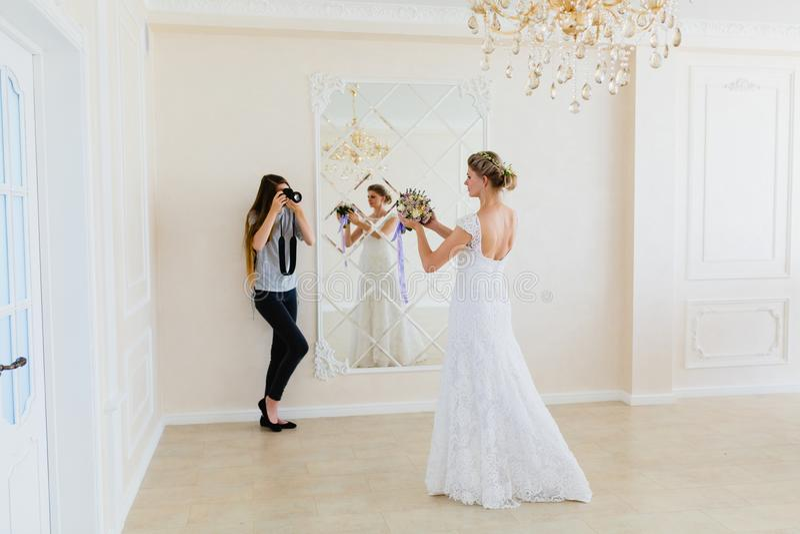 采取图片年轻性感的新娘的摄影师在演播室在镜子附近 免版税库存照片