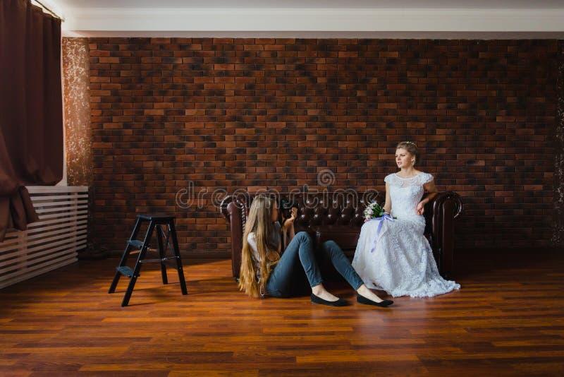 采取图片新娘的摄影师在一个大皮革沙发的演播室 库存照片