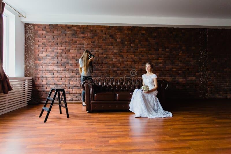 采取图片新娘的摄影师在一个大皮革沙发的演播室 免版税库存照片