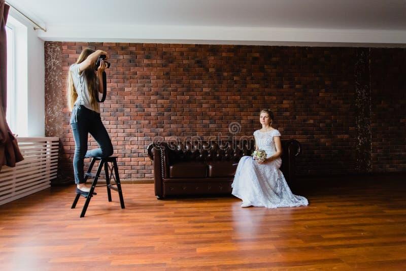 采取图片新娘的摄影师在一个大皮革沙发的演播室 库存图片