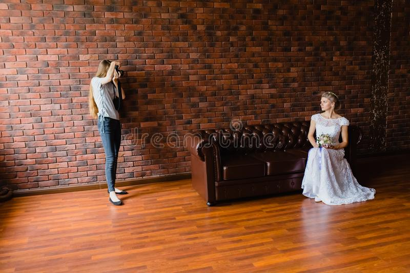 采取图片新娘的摄影师在一个大皮革沙发的演播室 免版税图库摄影