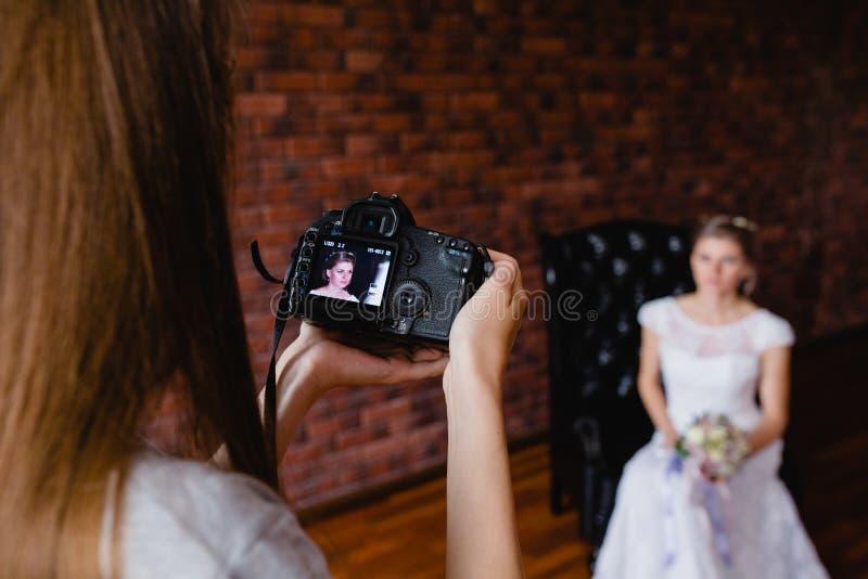 采取图片新娘的摄影师在一把大皮革扶手椅子的演播室 免版税库存图片