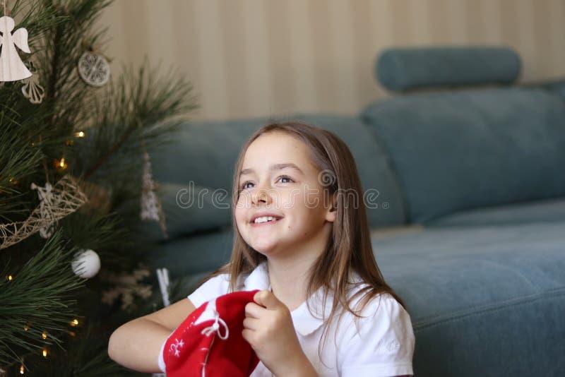采取圣诞节礼物的美丽的矮小的微笑的女孩在充满希望的红色传统袋子外面在她的眼睛 图库摄影