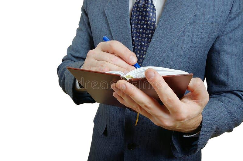 采取在一个小笔记本的商人的特写镜头笔记。 库存图片