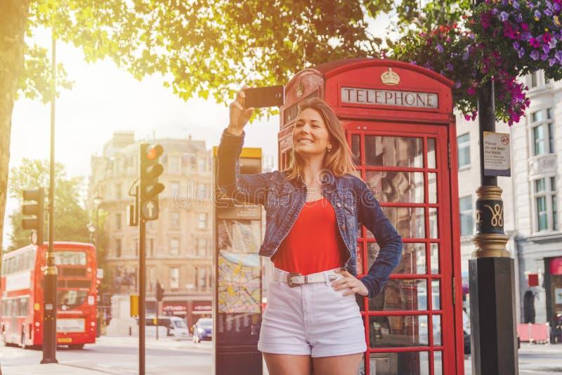 采取在一个电话箱子和一辆红色公共汽车前面的愉快的少女一selfie在伦敦 免版税库存照片