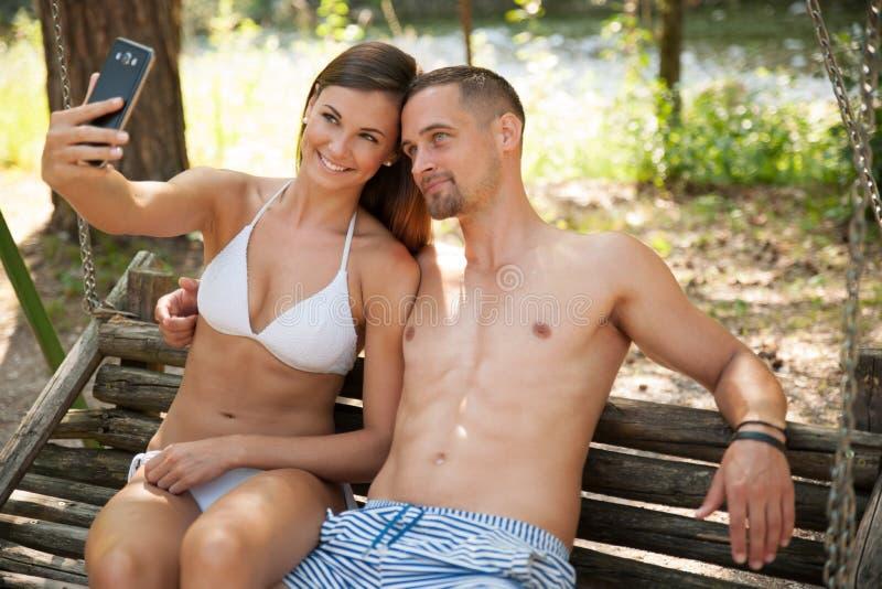 采取在一条长凳的活跃年轻夫妇selfie在公园在河附近 免版税库存图片