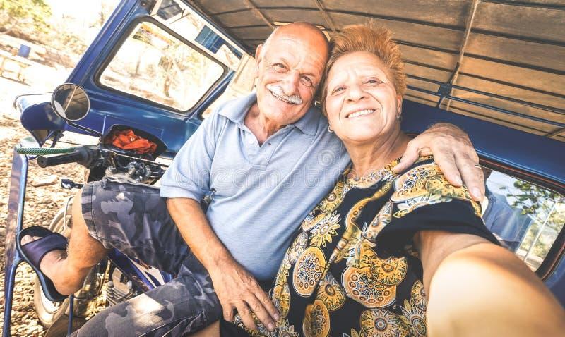 采取在三轮车的愉快的资深夫妇selfie在菲律宾旅行-活跃嬉戏的老人的概念在退休期间的- 免版税图库摄影