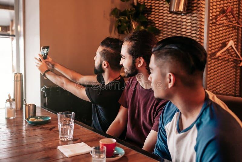 采取在休息室酒吧的小组阿拉伯朋友selfie 获得混合的族种年轻的人乐趣 最好的朋友住处一起 免版税库存照片