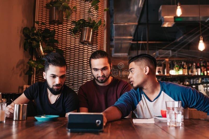 采取在休息室酒吧的小组阿拉伯朋友selfie 获得混合的族种年轻的人乐趣 免版税库存照片