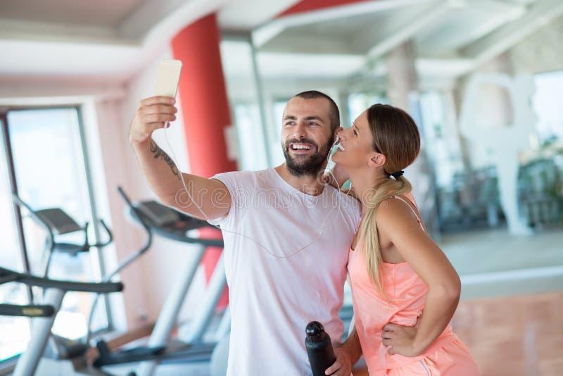 采取在健身房的年轻夫妇一sefie 免版税库存图片