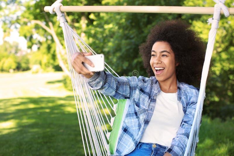 采取在吊床的美丽的年轻非裔美国人的妇女selfie户外 库存照片